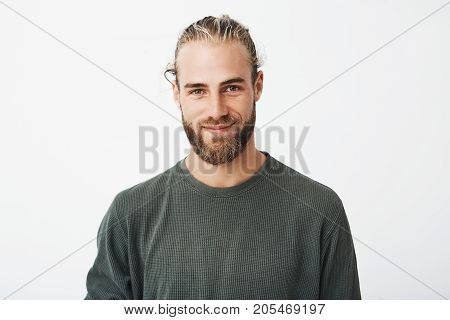 Portrait of beautiful mature blonde bearded guy with trendy hairdo in casual grey shirt smiling and looking in camera