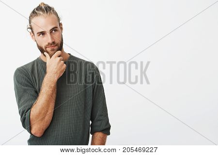 Attractive swedish guy with stylish hair and beard in grey shirt holding his chin and thoughtfully looking aside thinking about his future
