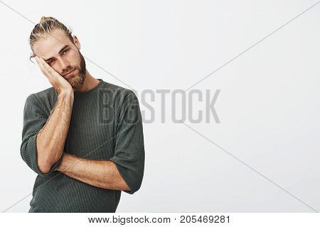 Beautiful young blonde man with stylish hairstyle and beard holding head with hand being tired after long and hard day at work