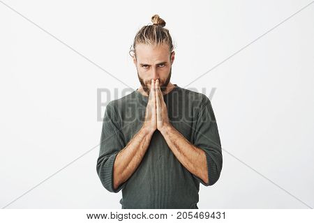 Upset attractive bearded guy with pressed hands in front of face begging boss not to firing him after a big mistake on work