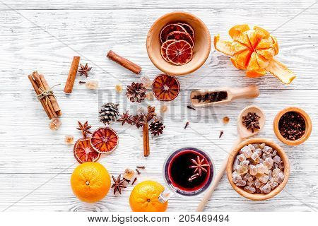 Merry christmas in winter evening with warm drink. Hot mulled wine or grog with fruits and spices on light desk background top view