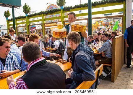 MunichGermany-September 242017: A waiter arrives at table carrying fresh Beer mugs in a Biergarten at the Oktoberfest