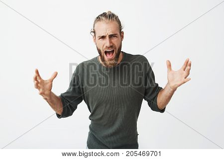 Good-looking attractive man with stylish hairstyle and beard screaming and cheering favourite rugby team in important match