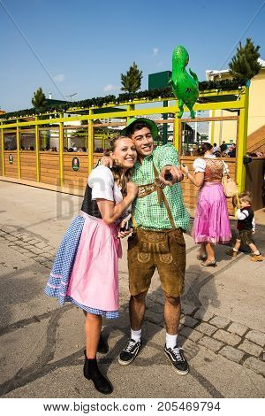 MunichGermany-September 242017: A couple in typical bavarian clothes pose for a photo at the Oktoberfest