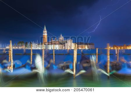 San Giorgio Maggiore church and gondolas in Venice, Italy during blue hour with dramatic sky and lighting. Focus on the church