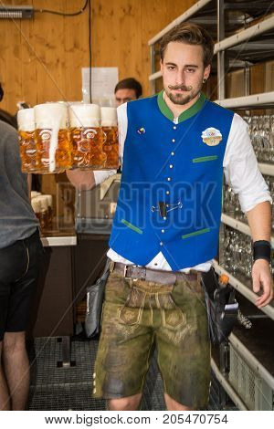 MunichGermany-September 242017: A waiter carries out five freshly draught Beer mugs in one hand at a serving station at the Oktoberfest
