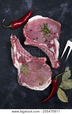 Heart shape Raw fresh meat Ribeye Steak with rosemary, pepper and salt on stone slate background , flat lay
