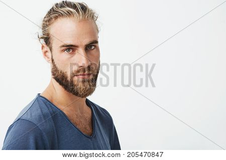 Close up of beautiful swedish man with stylish hairstyle and beard in blue t-shirt looking in camera with serious expression