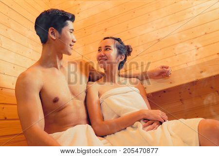 Young asian man and woman couple together sitting in sauna spa room with hot warm steam happy relaxing resting for health care and skin in holiday