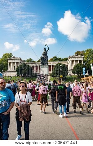 MunichGermany-September 242017: Crowds walk on the Oktoberfest grounds underneath the monument to the godess Bavaria