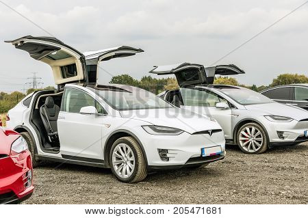 PRAGUE CZECH REPUBLIC - SEPTEMBER 23 2017. Two white cars Tesla Model X with opened door. Tesla Model X on the scraper car park.
