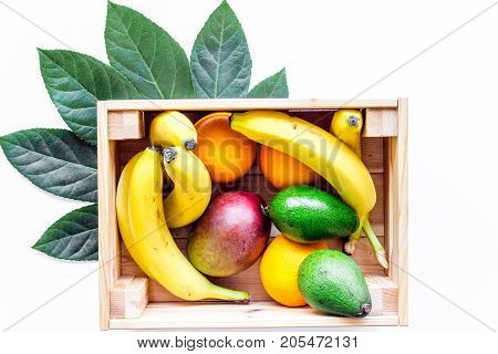 Sell friuts on the market. Bananas, oranges, mango in box on white background top view.