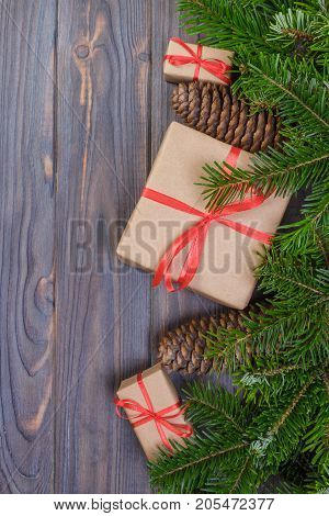 Christmas tree branch decorations and gift box on white wooden table.