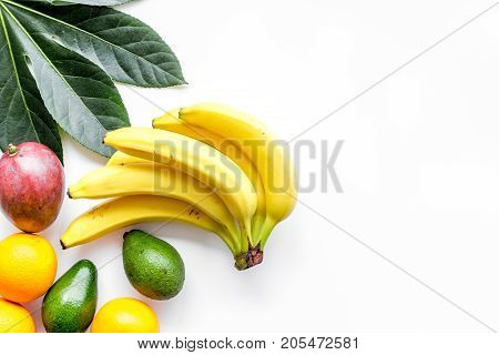 Tropical fruits background. Bananas, oranges, mango on white background top view.