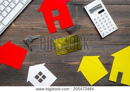 work desk with keyboard, keys and paper house figures for selling house set wooden background top view