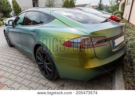 PRAGUE CZECH REPUBLIC - SEPTEMBER 23 2017. Tesla Model S gold and green color on airport runway in the evening. Tesla car.