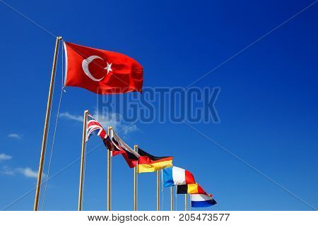 Flag of Turkey. Against the background of the blue sky a number of flags of tourists: Russia, England, Germany, France