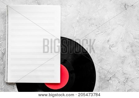 Workplace of musician. Music notes, vinyl record and coffee on grey background top view.