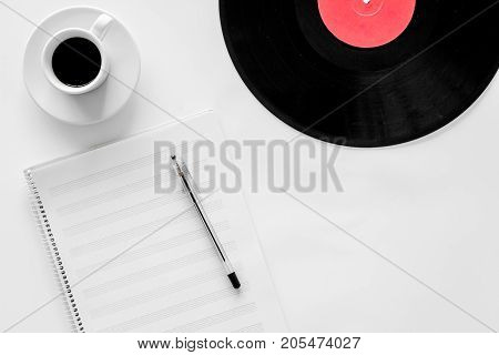 Workplace of musician. Music notes, vinyl record and coffee on white background top view.