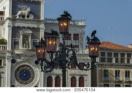 Venice, Italy - September 23, 2011: Column with lion of St Mark, symbol of imperial Venice,  Zodiac clock Tower and Mother of God in San Marco's square on the building, Venezia, Venice, Italy, Europe . Visit in place.