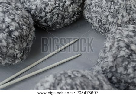 Woolen melange yarn and knitting needles on a gray background