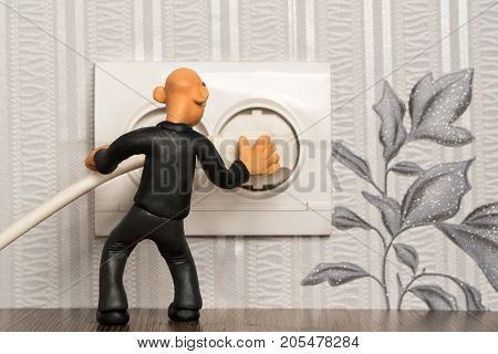Plasticine man sticks a plug in the socket in the wall of the apartment
