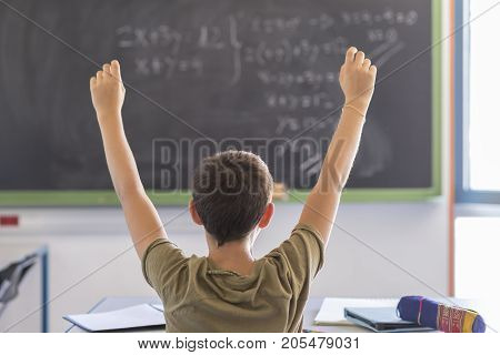 Student With Hands Up In Classroom During A Lesson