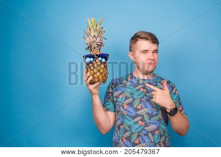 Funny man hold pineapple with sunglasses on blue background. Vacation, summer, vegetarians and detox concept.
