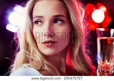 Young blonde girl with glass of champaigne at night party
