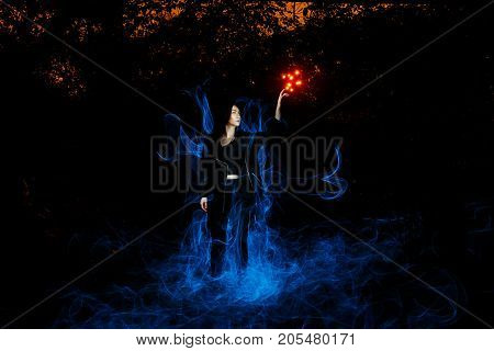 witch playing with lights like fire in the forest during halloween