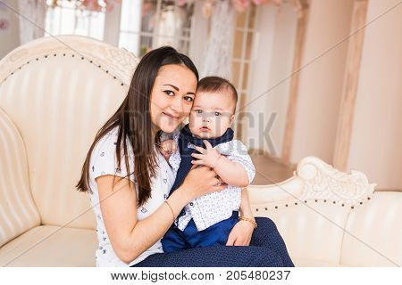 Lovely mother holding newborn baby in arms.