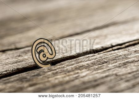 Small At Symbol Stuck In Between Wood