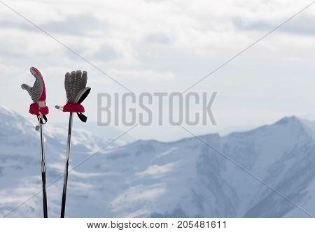 Gloves On Ski Poles And Snow Winter Mountains