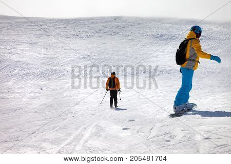 Snowboarder And Skier Downhill On Off-piste