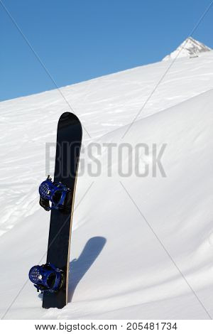 Snowboard In Snowdrift And Mountains At Nice Sun Day
