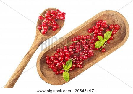 Ripe redcurrants on wooden plate with spoon on a white background. Top view