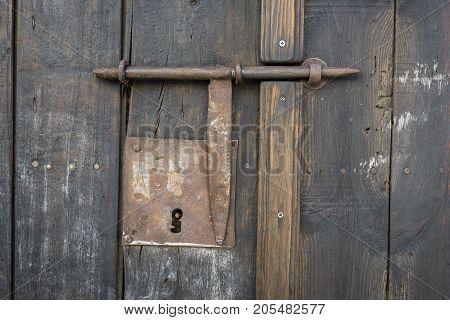 Closeup vintage door lock of external antique wooden door with a door pin lock, weathered on a Country house