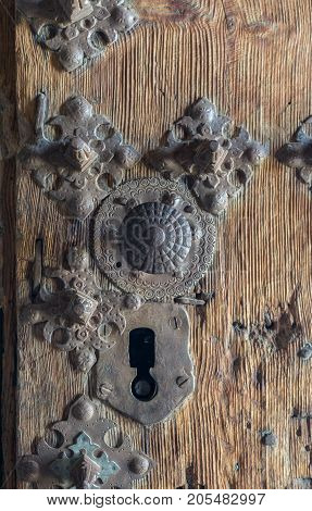 old iron lock, on a wooden door, with ornamental details in the shape of a flower