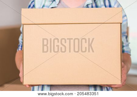 Close-up Of A Delivery Man Holding Cardboard Box.