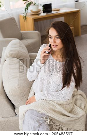 Portrait of beautiful brunet woman. Woman talking on the telephone with friends. Holiday morning.
