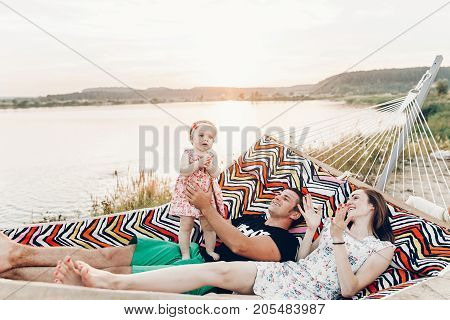 Cute, Emotional Baby Girl In Pretty Dress With Her Mother And Father In A Hammock On Vacation, Funny