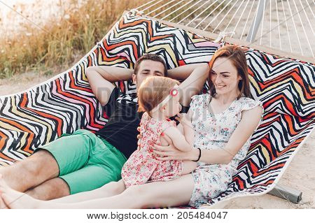 Happy Family Portrait, Young Hipster Father And Mother Lying In A Hammock With Their Baby Daughter,