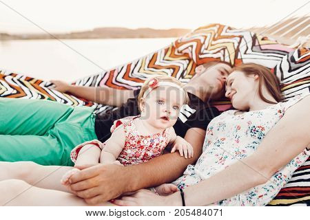 Adorable Baby Girl  Shocked Face, Lying With Her Happy Father And Mother, Young Hipster Couple Relax