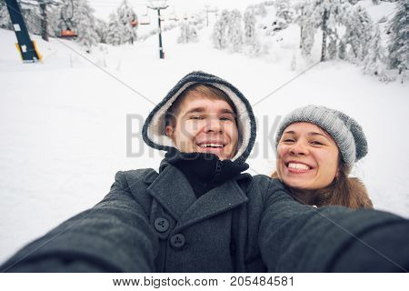 Young and happy couple doing winter selfie outdoor. Christmas, New Year and people concept.