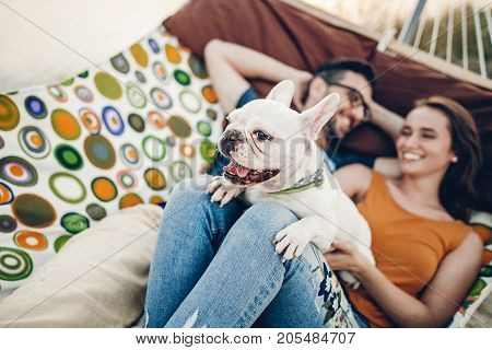 Cute Dog Smiling While On A Trip With His Owners, Joyful Young Family, Man And Woman Lying In Comfor