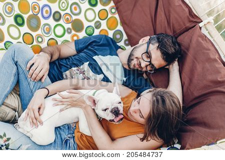 Happy Young Family Portrait, Cute Stylish Woman Holding Happy Bulldog Near Handsome Man In Sunglasse