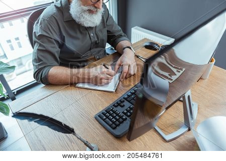 Creative process. Top view of working place of modern senior author is sitting at table with computer and writing in notepad with inspiration