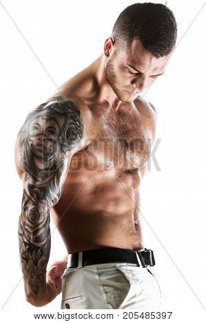 Studio shot of sexy muscular fitness model with tattooed torso. Young handsome man posing over white background.