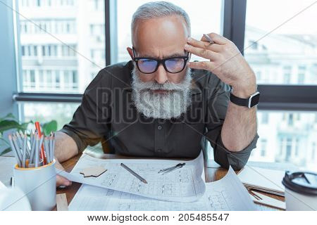 Responsible work. Portrait of serious mature man is holding building plan and looking at papers with concentration while touching his temple. He is sitting at table against window