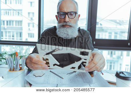 Professional glance. Concentrated old bearded engineer is holding plastic stencil while sitting at his working place with blueprints. Portrait